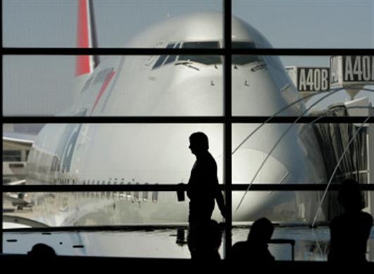 Persona pasando por una ventana en un aeropuerto al lado de avion