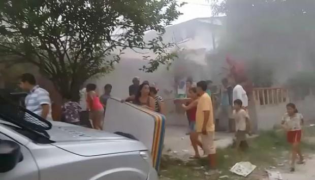 Personas a las afuera de una casa incendiada
