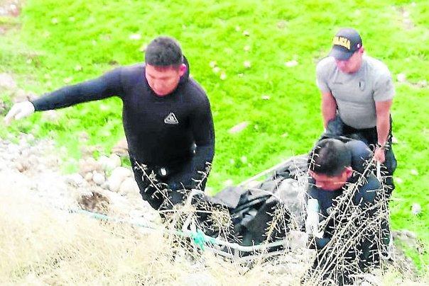 Personas levantando un cadaver del rio