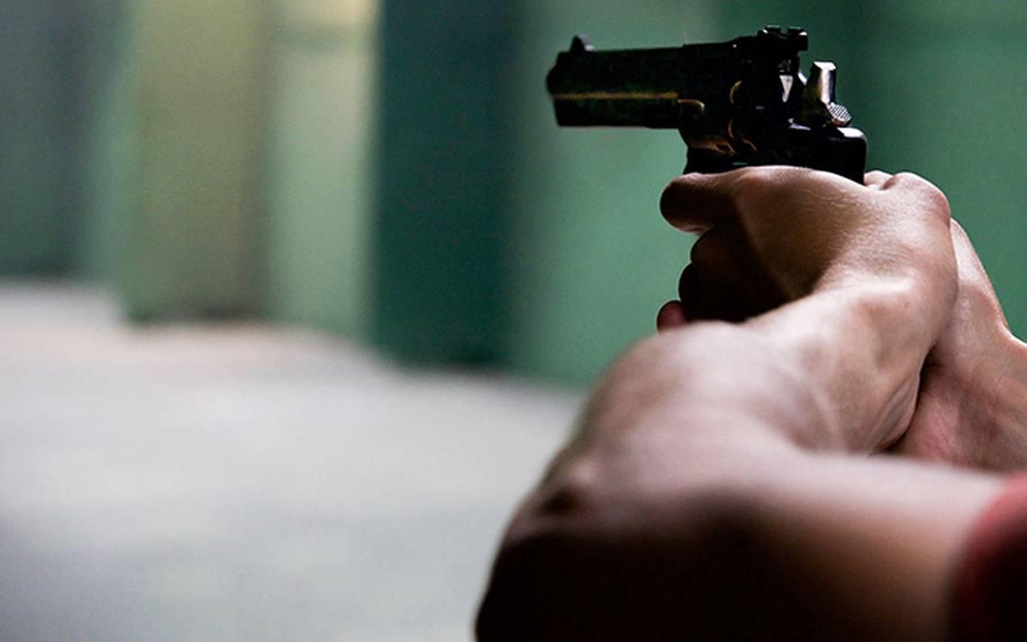 Pessoa segurando um arma de fogo