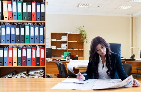 Mujer en un escritorio leyendo un periodico