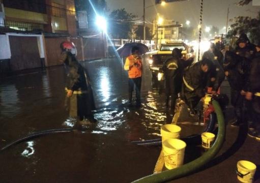 Personal de bomberos drenando alcantarilla