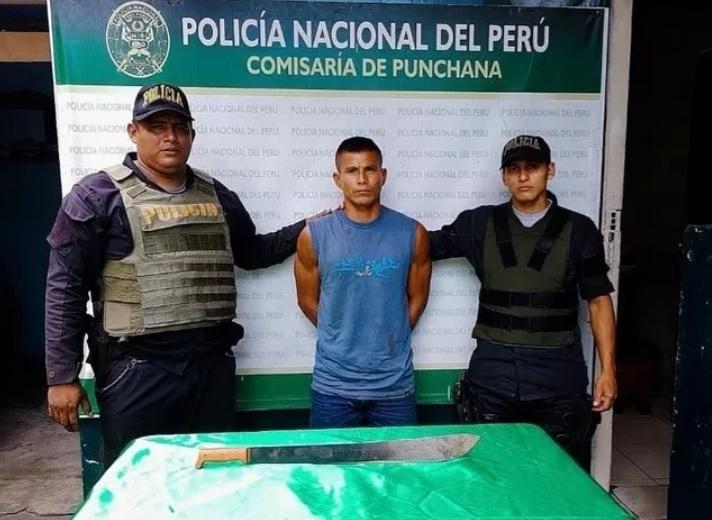 Policias al lado de un capturado por agresiones a su hija con machete