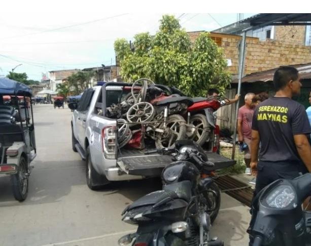 Personas a las afueras de un taller mecanico intervenido por oficiales
