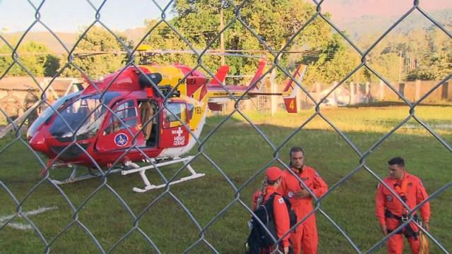 Pessoas ao lado de um helicoptero