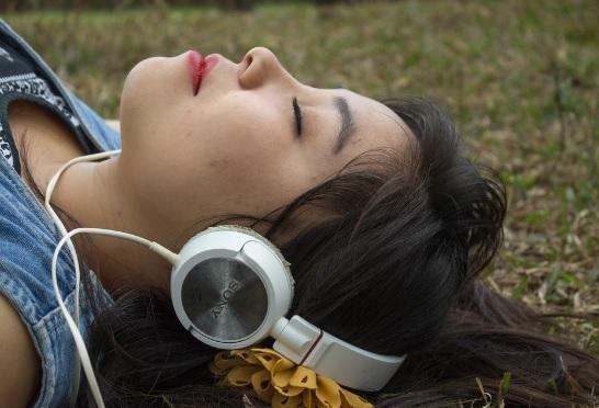 Mujer acostada escuchando musica por audifonos