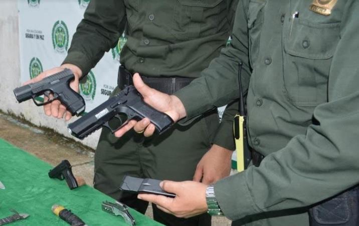 Dos policias sosteniendo cada uno un arma