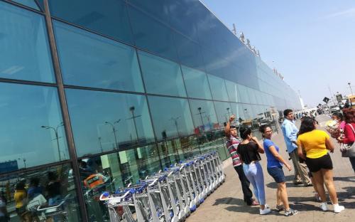 Personas caminando por las afueras del Aeropuerto de Lima