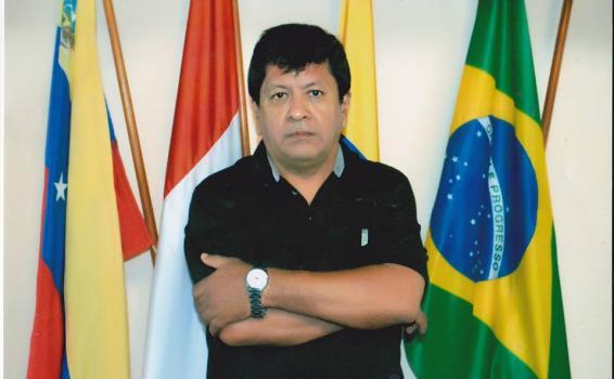 Alejandro Cueva Ramirez detras de tres banderas