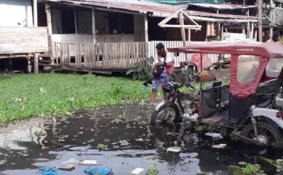 Persona cargando a un niño por el paso de inundaciones