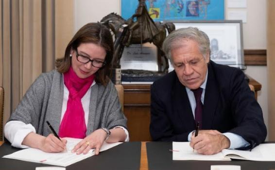 Dos personas firmando un acuerdo