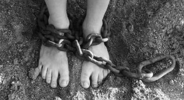 Persona con pies amarrados con unas cadenas