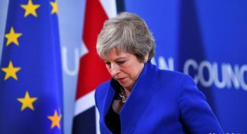 Theresa May caminando con la cabeza abajo