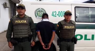 Persona capturada al lado de dos policías