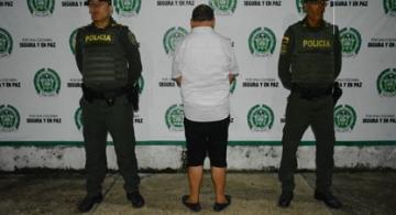 Persona de espaldas y al lado de dos policias en foto