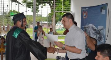 Persona entregando diploma a graduada