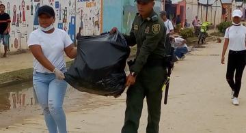 Policia y estudiante llevando una bolsa de basura llena