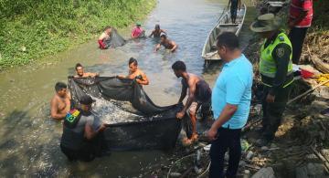 Personas a orillas del rio recogiendo peces