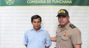 Policial al lado de un capturado