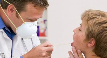 Medico examinado a niño con Sarampion